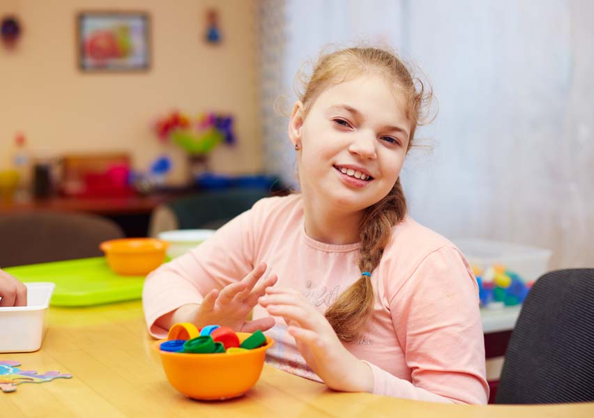 cute happy girl with disability develops the fine motor skills at rehabilitation center for kids with special needs