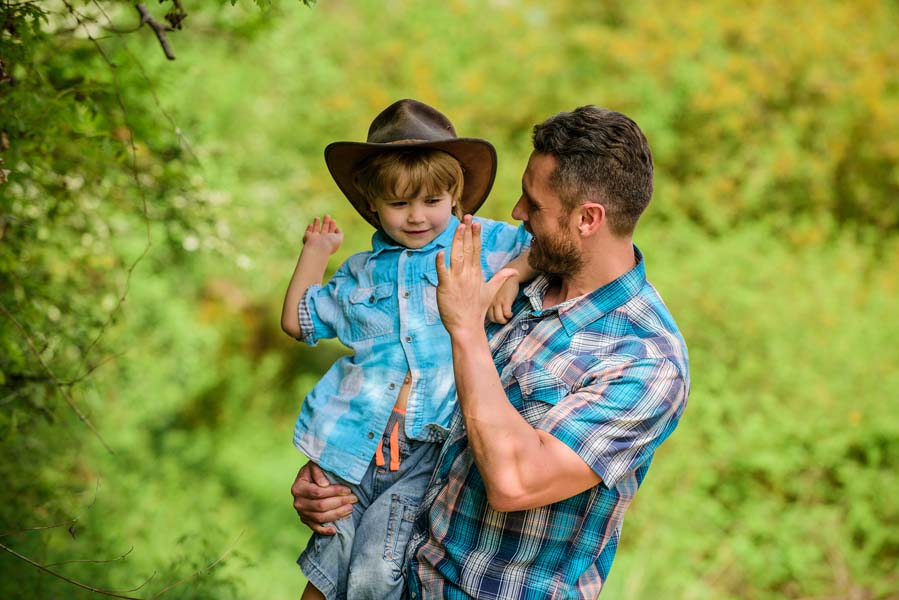 happy man dad in forest. human and nature. family day. happy earth day. Eco farm. small boy child help father in farming. father and son in cowboy hat on ranch. kid in rubber boots. ranch cowboy