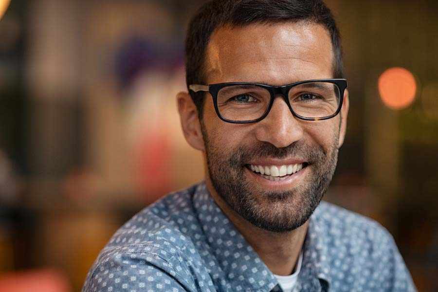 Young handsome man with big smile wearing eyeglasses and looking at camera. Close up face of happy business man wearing spectacles. Successful confident entrepreneur in casual clothing smiling.