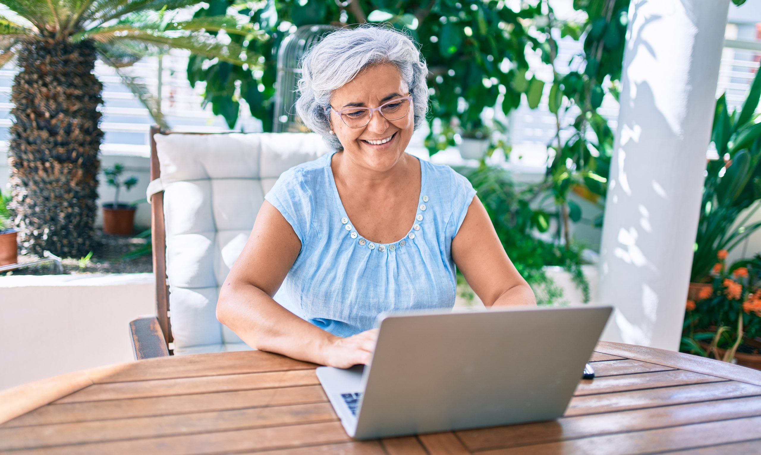 Middle age woman with grey hair smiling happy relaxing sitting at the terrace working from home