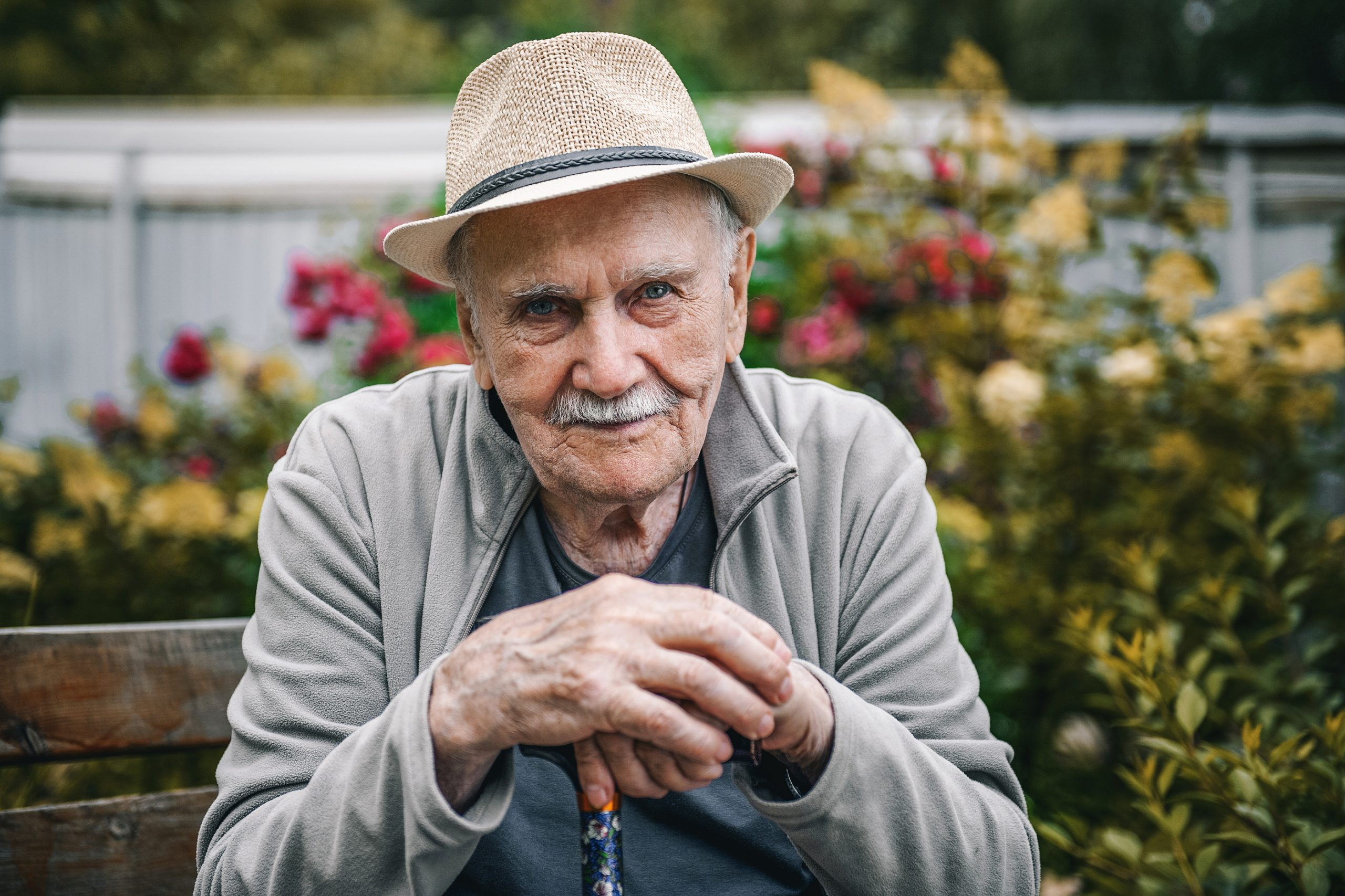 Portrait of a smiling and confident older 87-year-old handsome man in a hat with a mustache. Happy active old age. Portrait of a man in the autumn