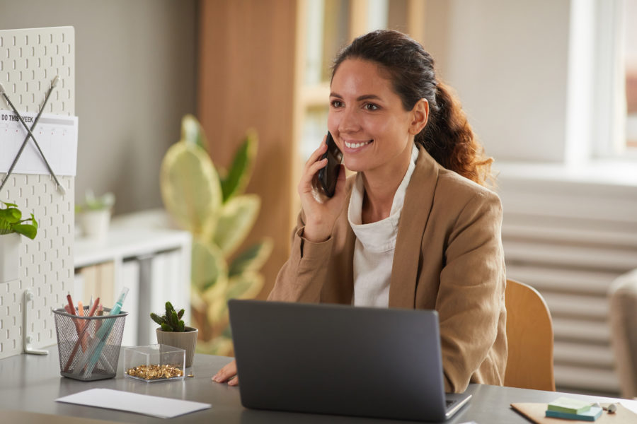 Portrait of modern businesswoman speaking by phone at workplace and smiling cheerfully while enjoying work in office, copy space