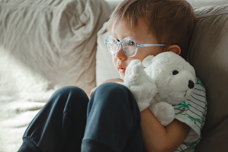 A child with autism in glasses sits on the sofa and is sad, angry and throws a soft toy dinosaur