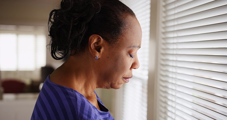 An older black woman mournfully looks out her window